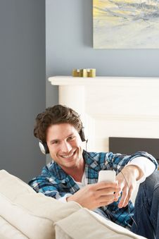 Free Man Listening To MP3 Player On Headphones On Sofa Royalty Free Stock Images - 14728989