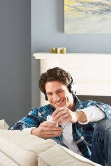 Free Man Listening To MP3 Player On Headphones On Sofa Royalty Free Stock Photography - 14729027