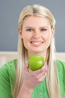 Free Woman Relaxing On Sofa Eating Apple At Home Royalty Free Stock Images - 14729309