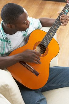 Free Man Relaxing Sitting On Sofa Playing Guitar Royalty Free Stock Image - 14730936