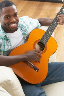 Free Man Relaxing Sitting On Sofa Playing Guitar Stock Image - 14731001