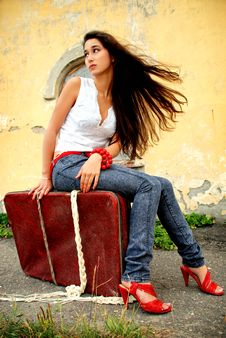 Charming Model Sitting On Red Suitcase. Royalty Free Stock Images