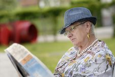 Free Senior Woman Reading A Newspaper In The Garden Royalty Free Stock Images - 14763229