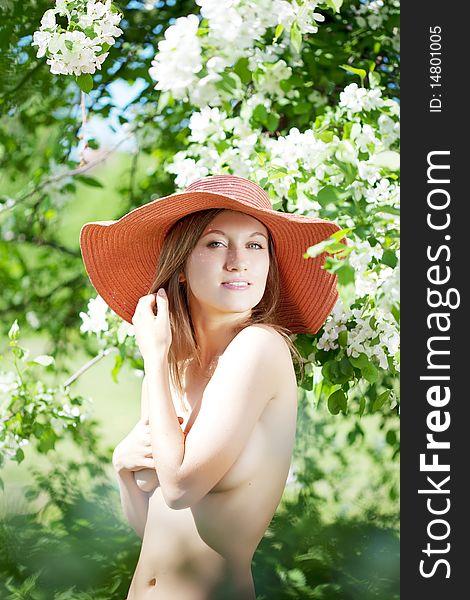 Beautiful half-naked woman among flowering gardens