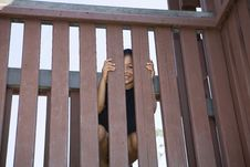 Free Little Girl Peeking Between Slats Of A Wooden Fenc Stock Photography - 14811412