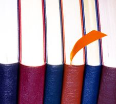 An Orange Bookmark And Six Leather Bound Books Royalty Free Stock Images