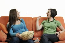 Free Girls Playing Hand Games On Orange Sofa Royalty Free Stock Photography - 14845777