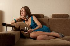 Free The Young Woman With A Wine Glass Sits On A Sofa Royalty Free Stock Photography - 14856787