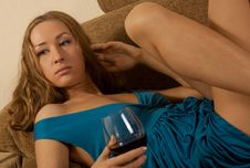 Free Young Woman With A Wine In Glass Sits On Sofa Royalty Free Stock Photography - 14856887