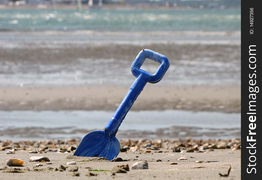 Blue shovel in the sea sand