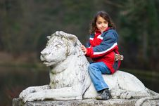 Young Girl Riding On Back Of Stone Lion Royalty Free Stock Photo