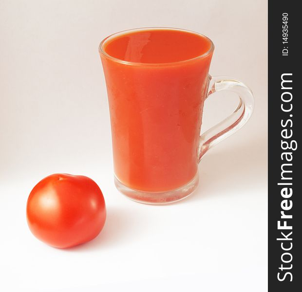 Red tomato and a glass of tomato juice