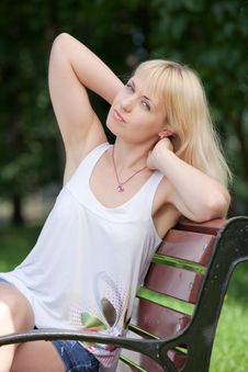 Free Pretty  Blond Woman Sits With Raised Arms On Park Stock Photos - 14941133