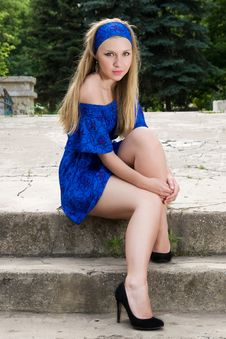 Free Pretty Young Woman In Blue Dress Sitting Outdoors Royalty Free Stock Photo - 14948735