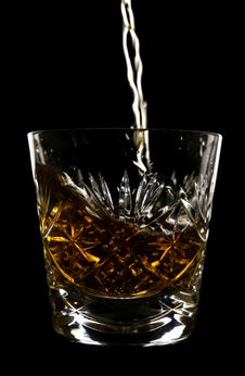 Whiskey Being Poured In Crystal Glass Royalty Free Stock Image