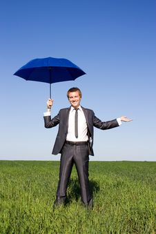 Businessman With Blue Umbrella In Field Stock Photography