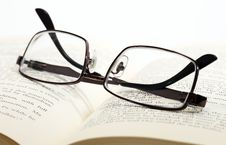Glasses On An Open Book Closeup Stock Images