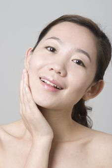 Smiling Asian Girl Touching Her Chin Royalty Free Stock Image