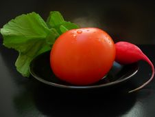 Free The Red Tomato With Radish On A Black Plate Stock Image - 15017451