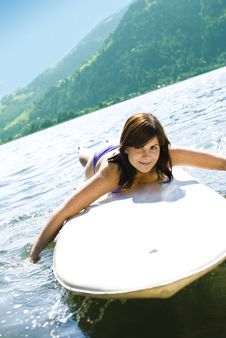 Girl Relaxing On Surfboard Stock Images