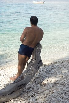 Man Leang On Tree On A Pebbly Beach In Paxos Greec Royalty Free Stock Image