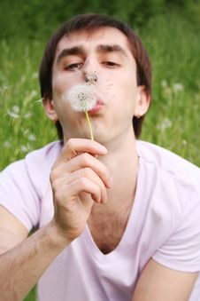 Free Young Man Blowing At Dandelion Focus On Flower Stock Photo - 15033300