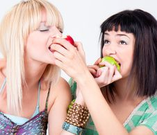 Two Young Pretty Women Bite A Apples Royalty Free Stock Photography