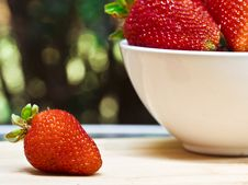 A Strawberry Next To A Bowl Of Strawberries Stock Photography