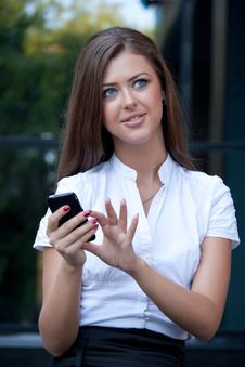 Free Young Woman Smiles With Phone In Hands Stock Images - 15059074