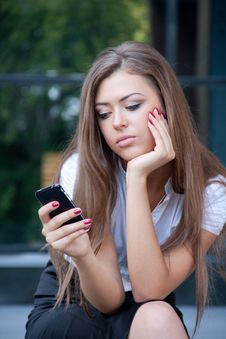 Free Young Woman Looks In Phone And Longs Royalty Free Stock Images - 15059139