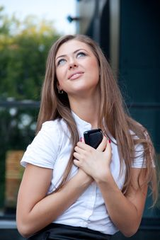 Free Young Woman With Phone In Hands Smiles Royalty Free Stock Photography - 15072877