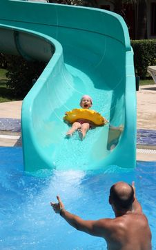 Father Catches Child On Water Slide Stock Photos