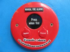 Red Fire Alarm Bell Sign  On The Blue Wall Stock Photography