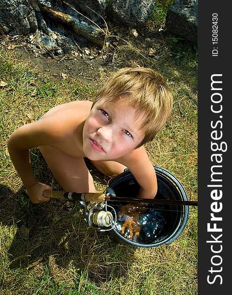 Boy with a bucket and a fishing rod