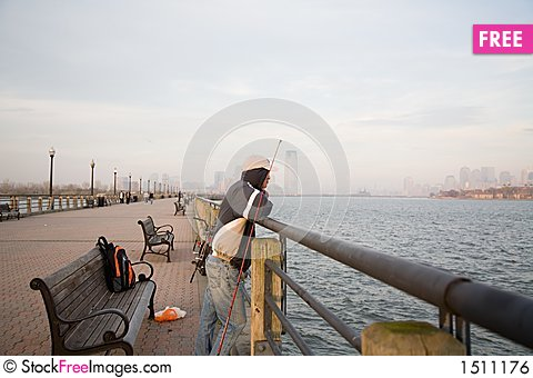 Lonely Man Fishing in Sunset Stock Photo