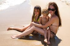 Young Family Sitting At The Beach Stock Photo