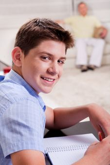 Young Boy In Focus, Studying And Smiling At Camera Royalty Free Stock Image