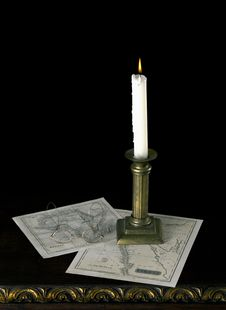 A Candle With Old Maps  In Old Candlestick On Old Royalty Free Stock Image