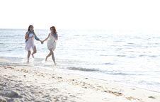 Two Beautiful Girls Running On The Beach. Stock Photos