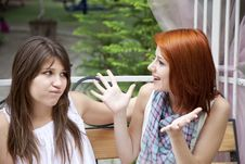 Two Girls Gossiping On Bench At Garden. Stock Photography