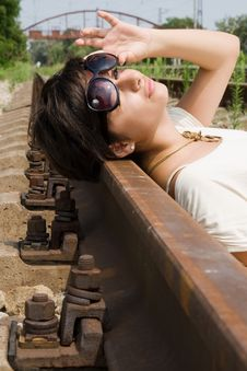 Girl Laying Carelessly On The Railroad Stock Photo