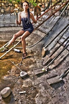Attractive Woman In A Stone Hole Among Old Shovels Royalty Free Stock Images