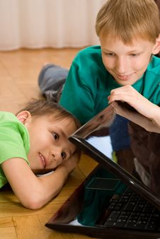 Brothers Lie  With Laptop Stock Image