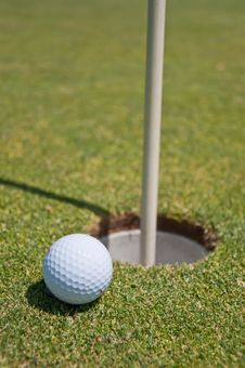 Golf Hole With Ball And Flag Royalty Free Stock Photo