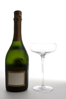 Champagne Bottle Next To An Empty Glass Royalty Free Stock Photos