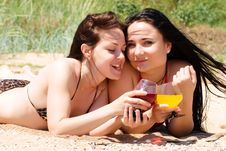 Two Young Girls Drink Cocktails At The Beach Stock Photo