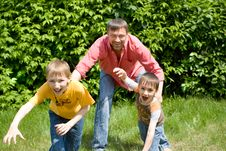 Father Playing With Two Children Stock Photo