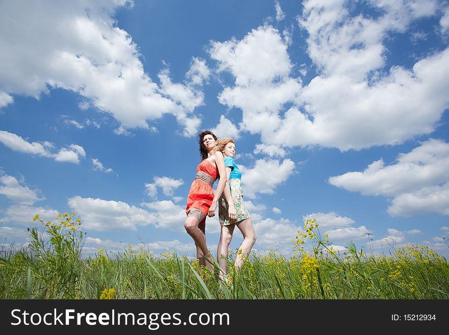 Two beautiful women standing  on summer field