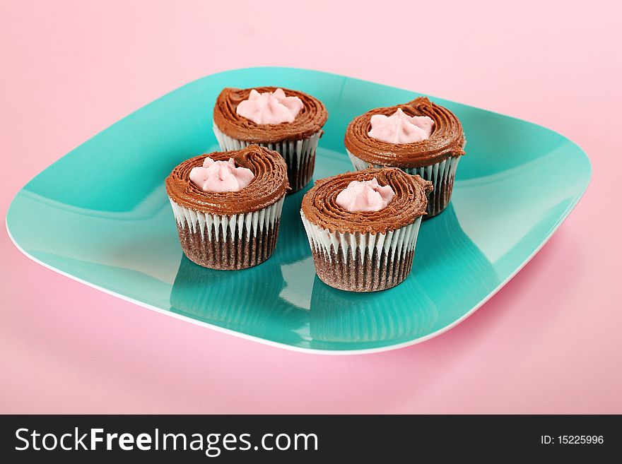 Chocolate cupcakes on pink background