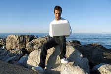 Free Young Man Using Laptop At Beach Royalty Free Stock Images - 15241419